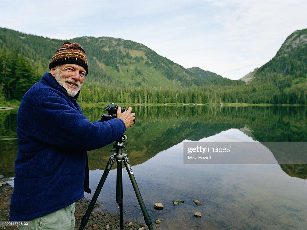 Senior man setting up camera by lake, looking over shoulder : Stock Photo