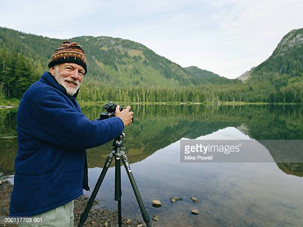 Senior man setting up camera by lake, looking over shoulder