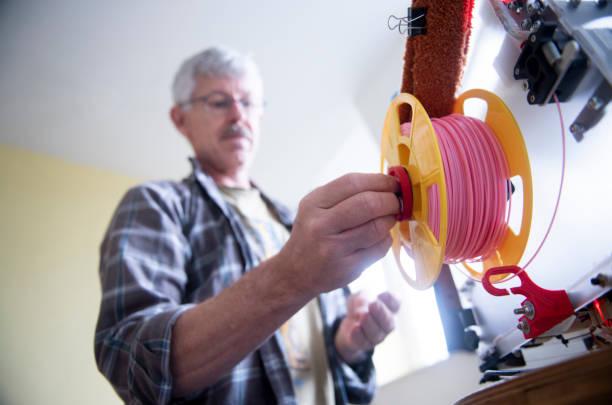 Senior man setting up his 3D-printer: attaching a new filament spool