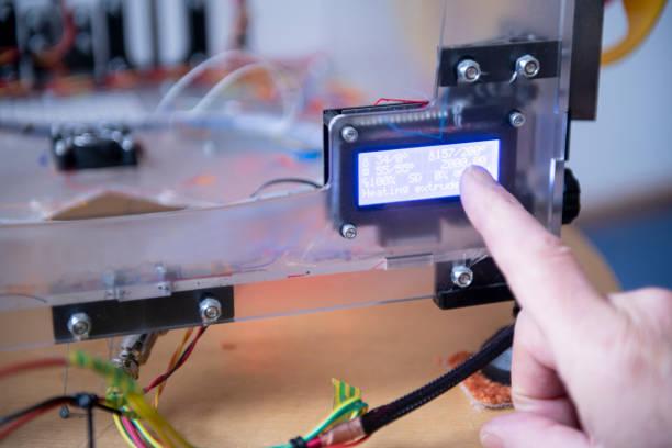 Senior man setting up his 3D-printer, pointing at the screen