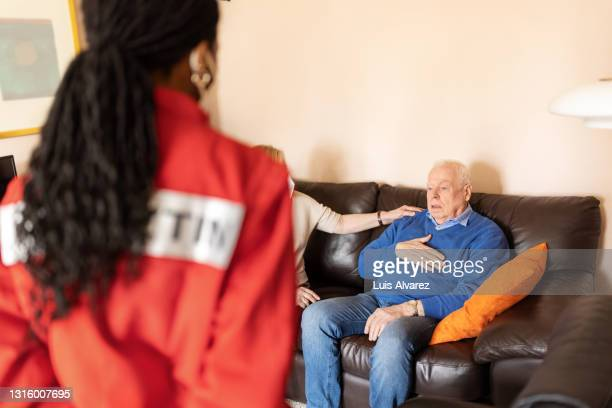 senior man sharing his health issues with doctor on home visit - long hair stock pictures, royalty-free photos & images