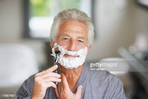 senior man shaving face - shaving stock pictures, royalty-free photos & images