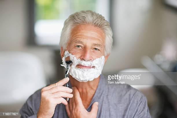 Senior man shaving face