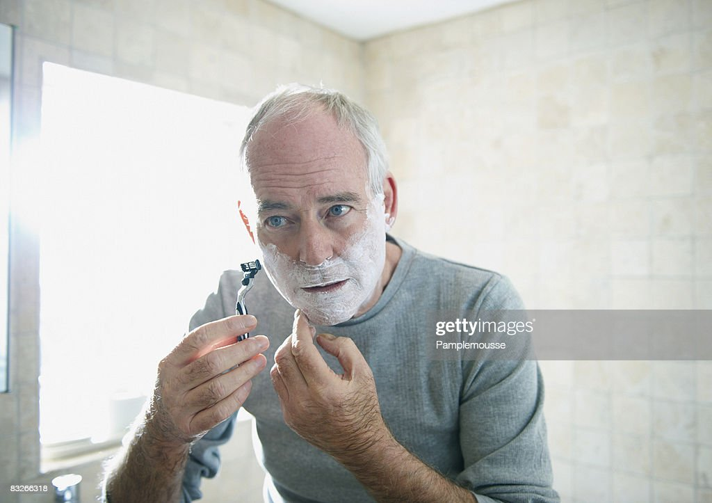 Senior man shaving : Bildbanksbilder