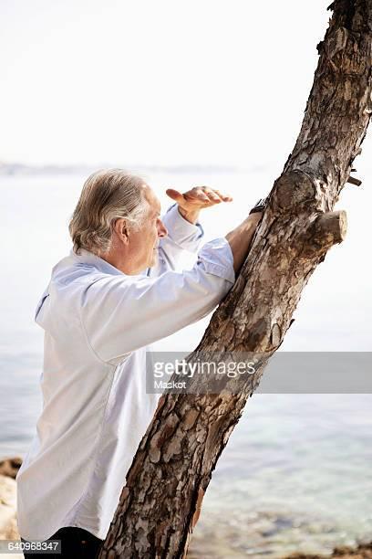 Senior man shielding eyes while looking at view