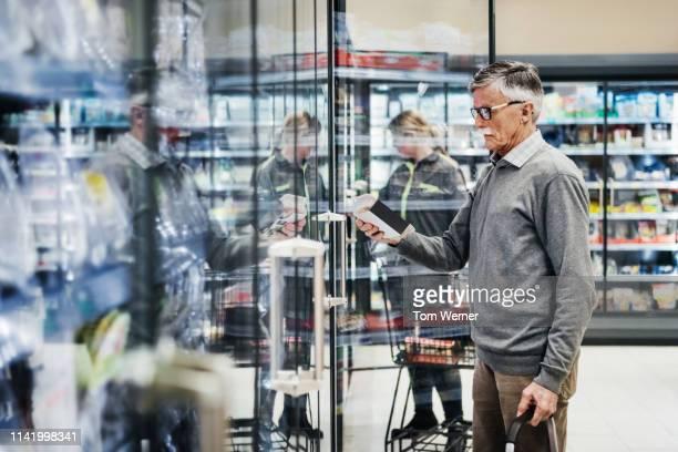 senior man shopping in frozen food section - tragen stock-fotos und bilder