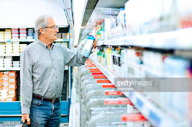 senior man shopping in supermarket - consumentisme stockfoto's en -beelden