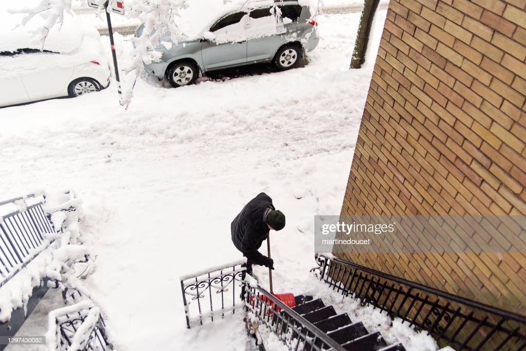 Senior man shoveling snow from stair case on city street. : Stock Photo
