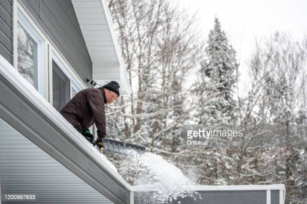 senior man shoveling snow in winter after snowstorm - snow shovel stock pictures, royalty-free photos & images