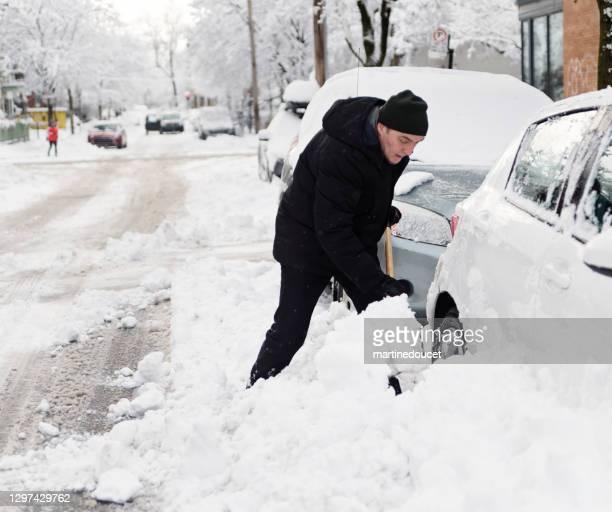 """街の通りで車の周りに雪かきシニアマン。 - """"martine doucet"""" or martinedoucet ストックフォトと画像"""