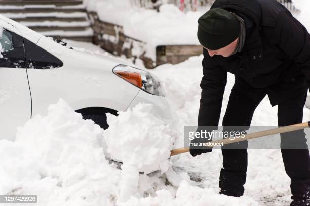 "senior man shovelling snow around car on city street. - ""martine doucet"" or martinedoucet stock pictures, royalty-free photos & images"