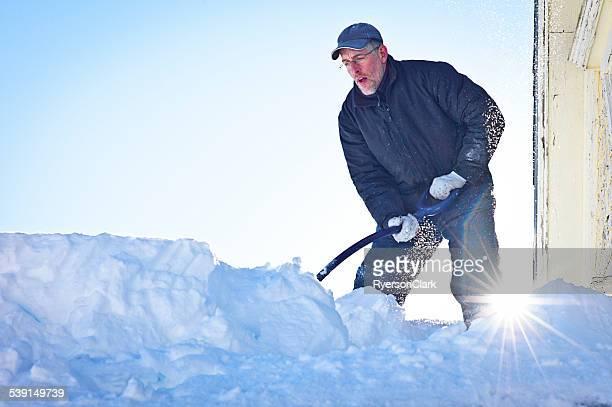 Senior Man Shovels 雪のルーフトップ。