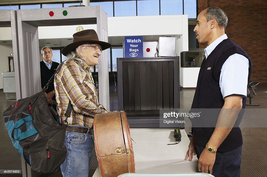 Senior Man Showing Luggage to a Customs Officer at an Airport : Stock Photo