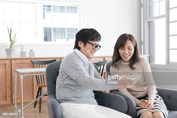 Senior man showing mobile phone to mature woman
