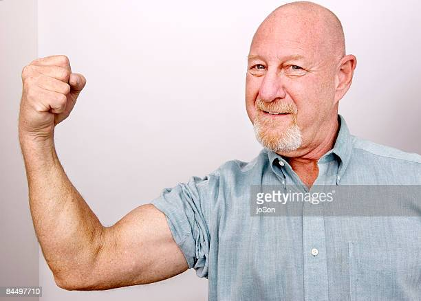 Senior man showing muscle arm , portrait