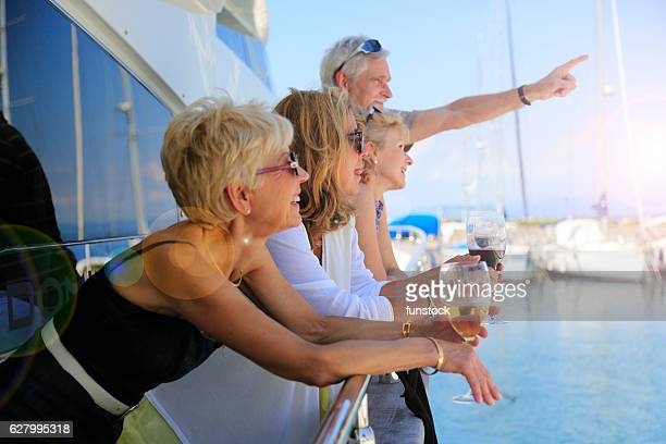 senior man showing something to their friends on a yacht - marina stock photos and pictures