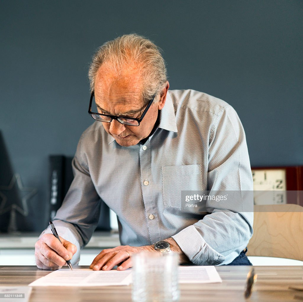Senior man signing document at table in house : Stock Photo