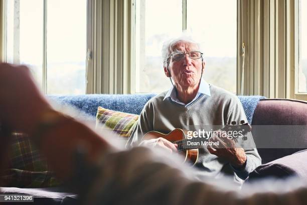 senior man singing and playing guitar for a woman at home - hobbies stock pictures, royalty-free photos & images