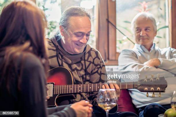 Senior man singing and playing guitar for his friends