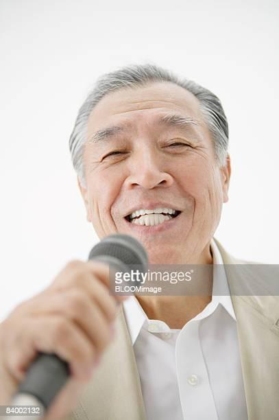 Senior man singing into microphone, studio shot