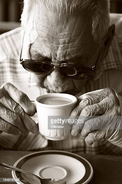 Senior Man Sips Coffee with Bandage Injury and Sunglasses