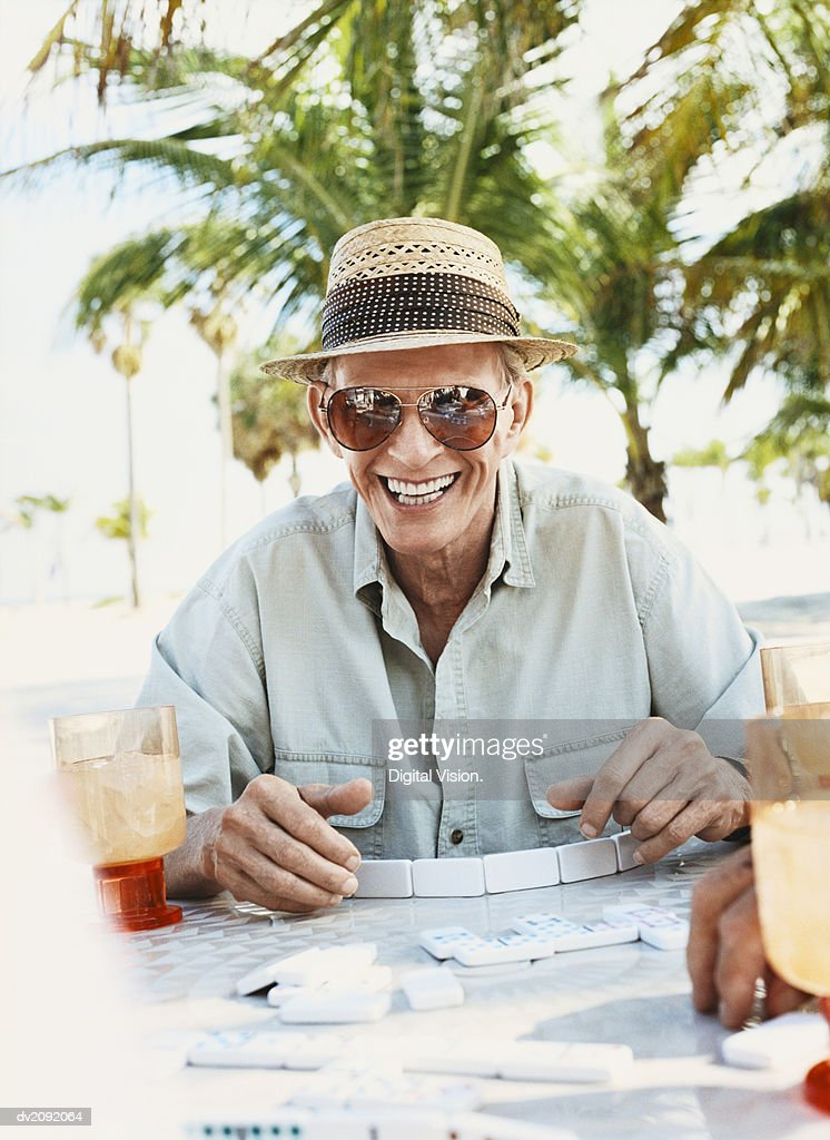 Senior Man Sits at an Outdoor Table Playing Dominoes, Laughing : Stock Photo