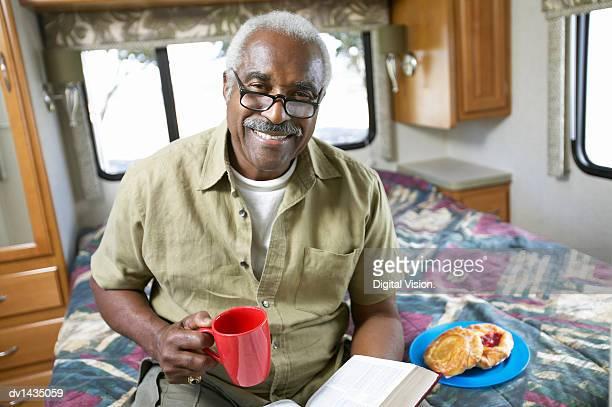 senior man sits on a bed in a motor home, having a snack and reading a book - wohngebäude innenansicht stock-fotos und bilder