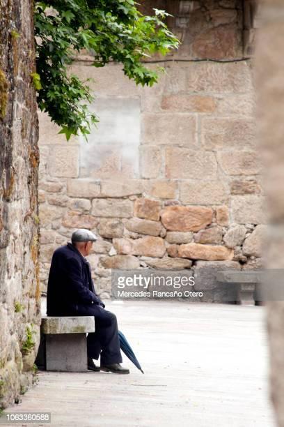 senior hombre sentado solo en el banco en un callejón estrecho. - pueblo fotografías e imágenes de stock