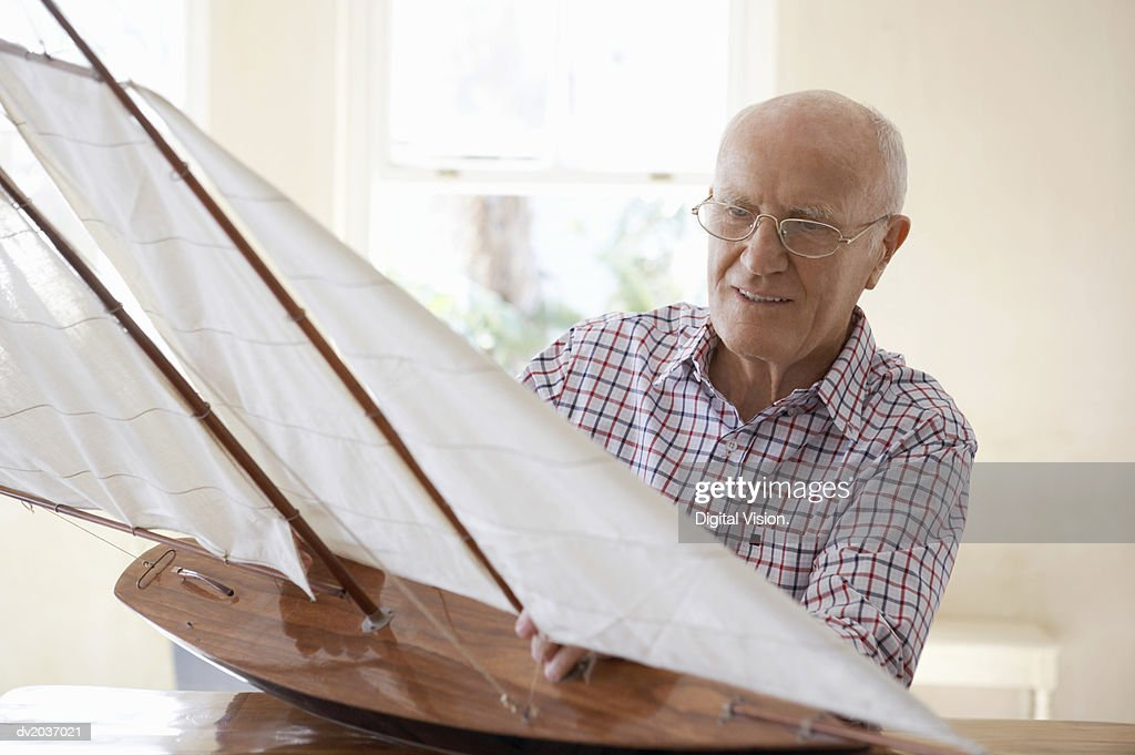 Senior Man Sitting at a Table and Examining a Model Yacht : Stock Photo