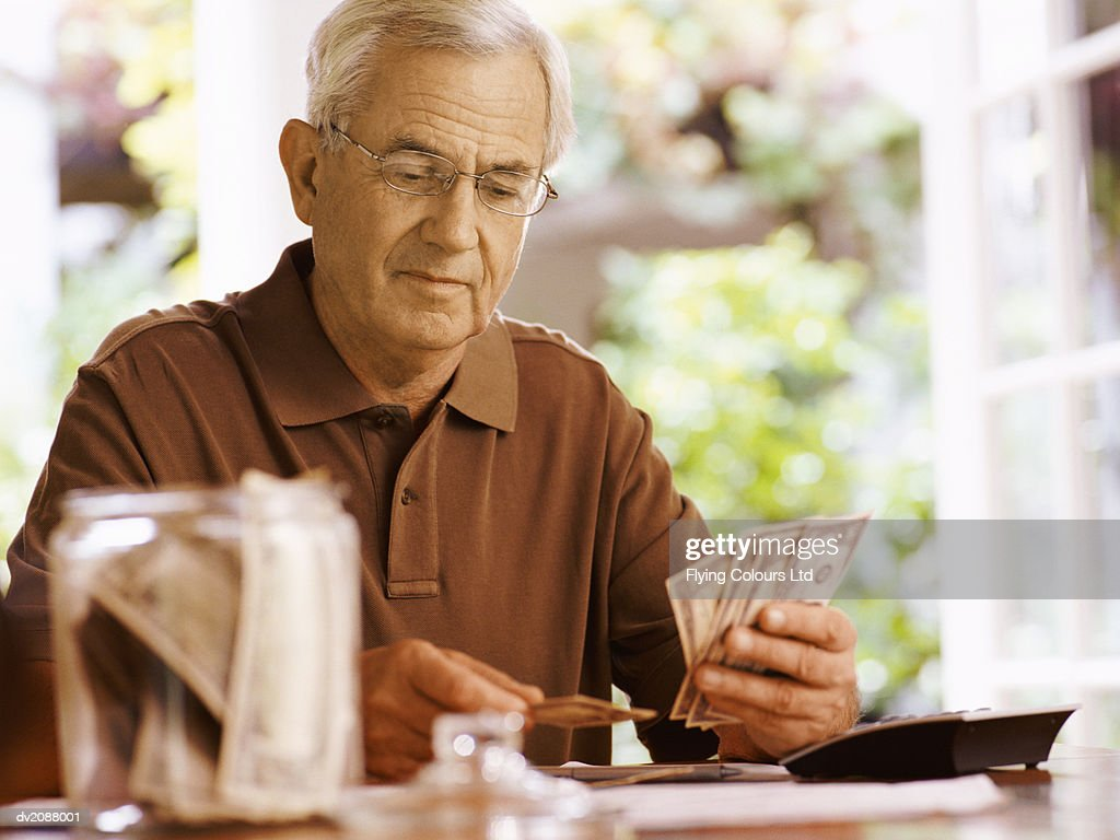 Senior Man Sitting at a Table Counting Dollar Bills : Stock Photo