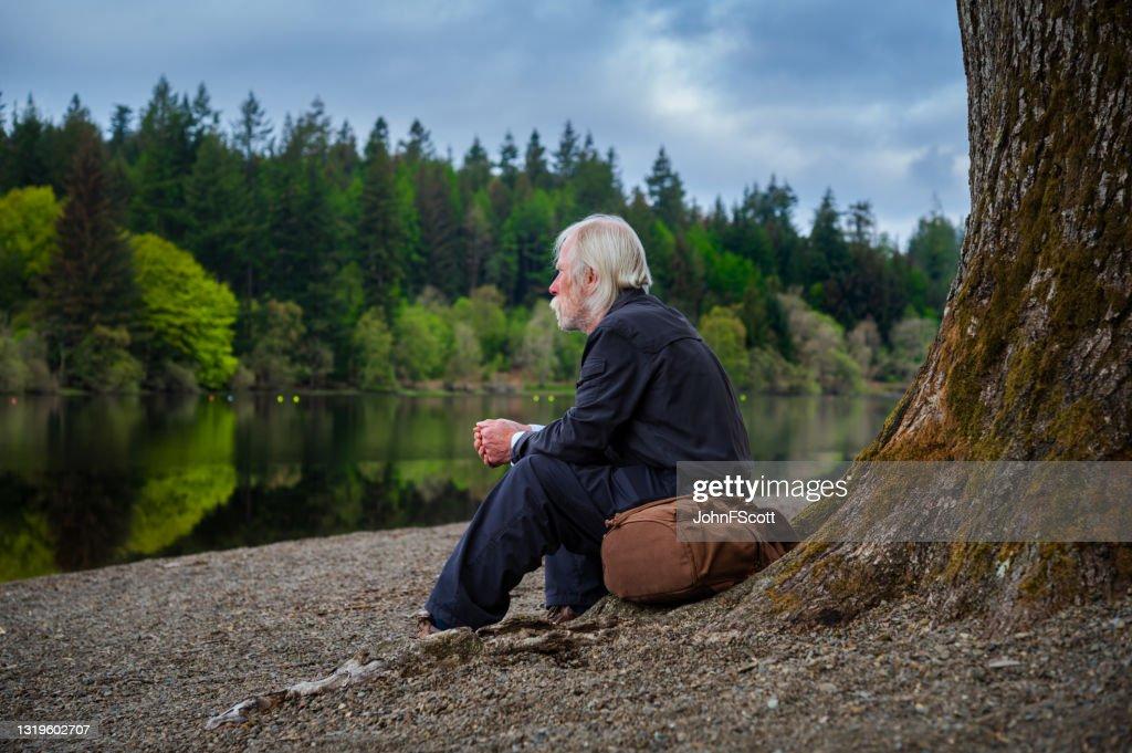Senior man sitting at a tree beside a lake : Stock Photo