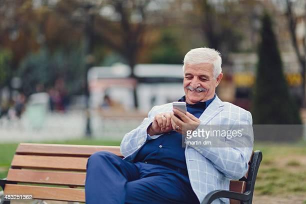 Senior man sitting at bench and using smartphone
