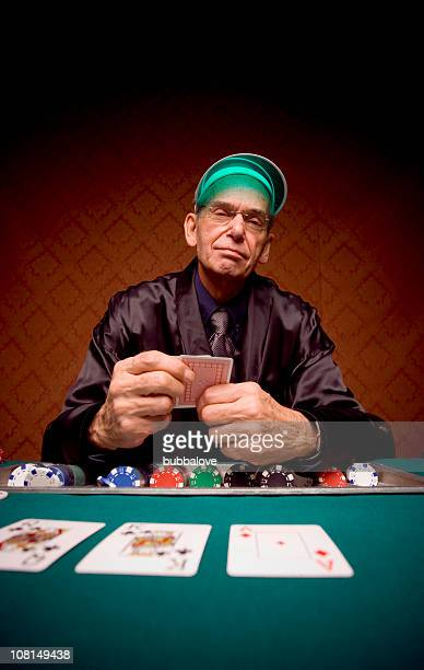 senior man sitting at card table and playing poker - smoking jacket stock photos and pictures