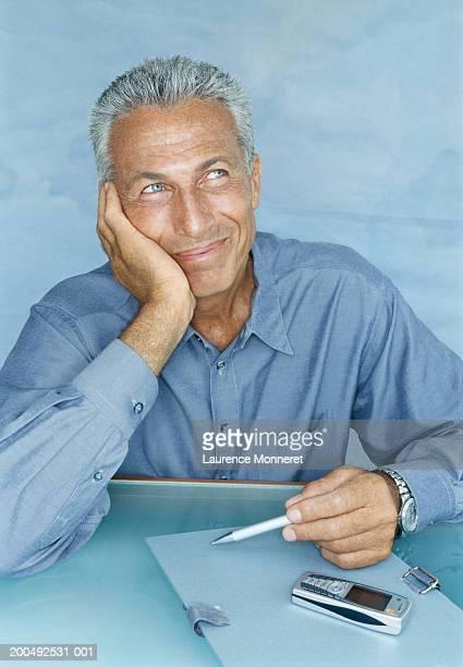 Senior man sitting at desk, holding pen, resting head on hand