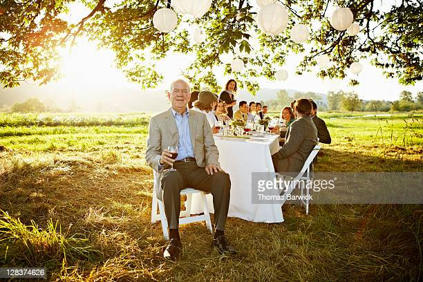 senior man sitting at head of table outside - prosperity stock pictures, royalty-free photos & images