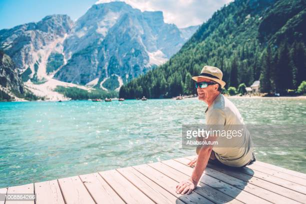 senior man sitting at lake  braies in the dolomite alps, south tyrol, italy, europe - pragser wildsee stock pictures, royalty-free photos & images