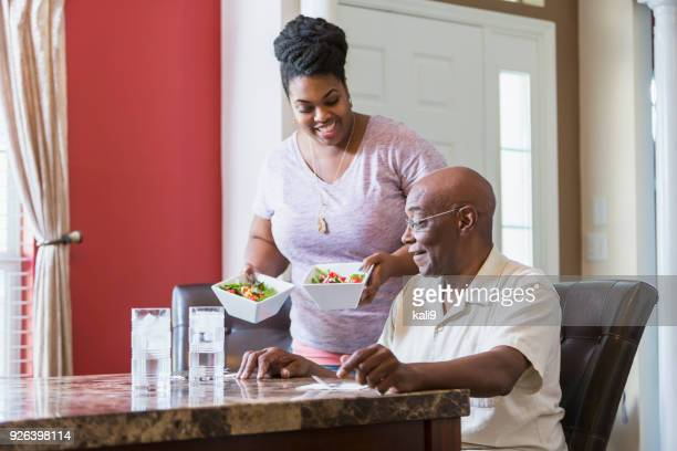 senior man sitting at table, adult daughter serving food - home caregiver stock pictures, royalty-free photos & images