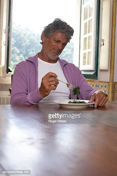 Senior man sitting at table in front of plate with spinach, making face