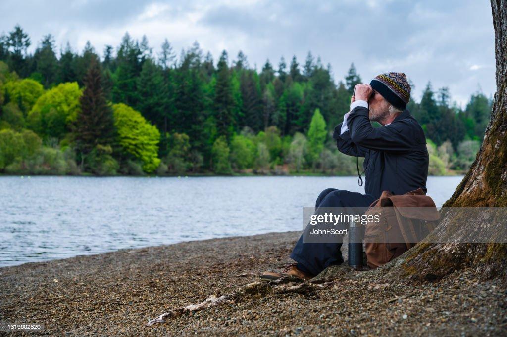 Senior man sitting beside a lake using binoculars : Stock Photo