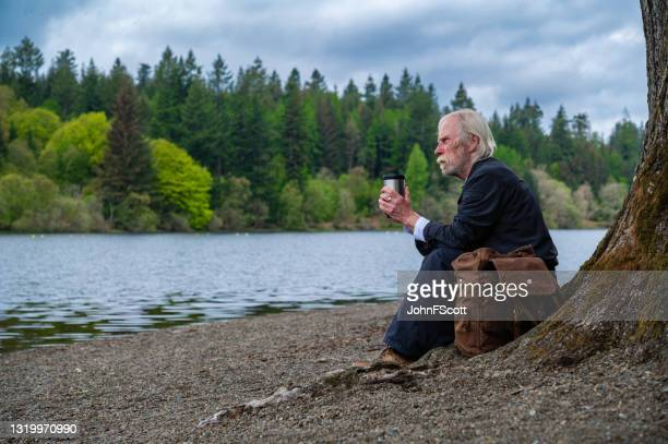 senior man sitting beside a loch - johnfscott stock pictures, royalty-free photos & images
