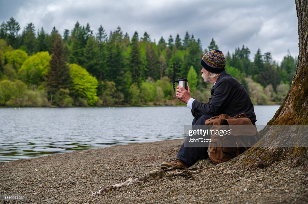 Senior man sitting beside a loch : Stock Photo