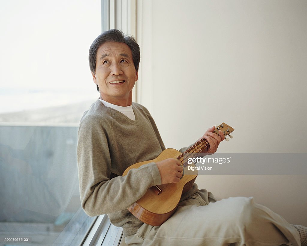 Senior man sitting by window playing ukelele, looking up : Stock Photo