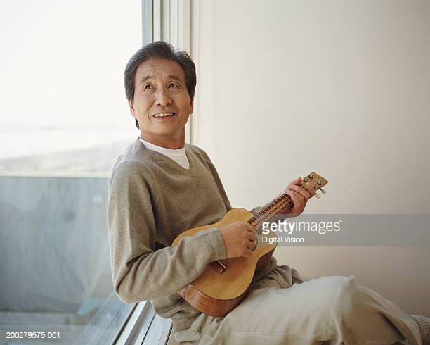 Senior man sitting by window playing ukelele, looking up