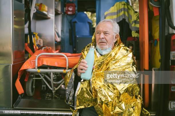 senior man sitter i en ambulans uppvärmning med termisk filt och varm dryck - victim bildbanksfoton och bilder