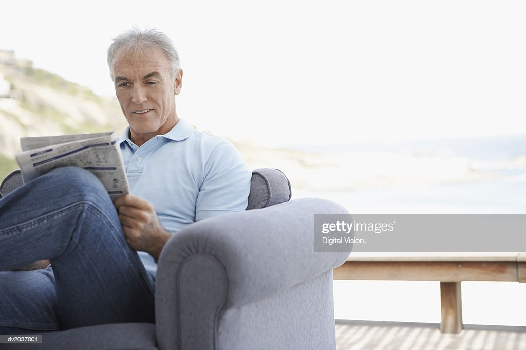 Senior Man Sitting in an Arm Chair on a Patio and Reading a Newspaper : Stock Photo