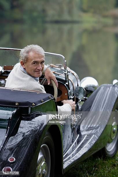 Senior man sitting in antique car