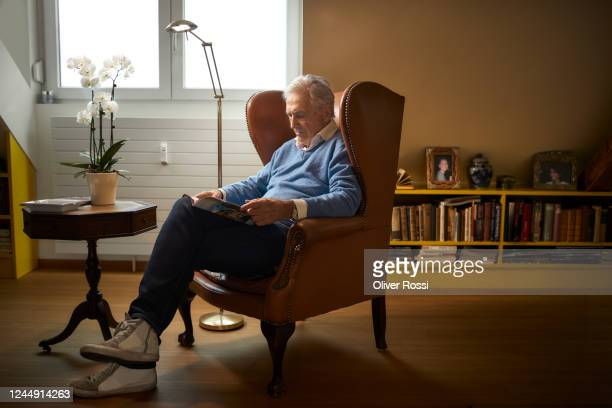 senior man sitting in armchair at home reading magazine - chair stock pictures, royalty-free photos & images