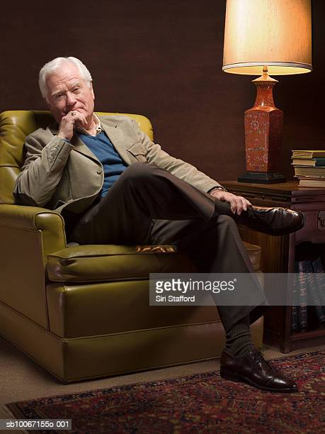 Senior man sitting in armchair, portrait