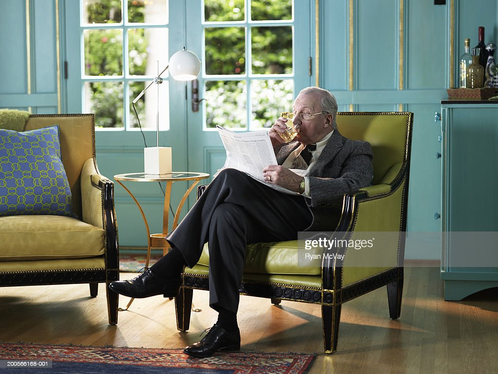 Nice Senior Man Sitting In Armchair Reading Newspaper : Stock Photo
