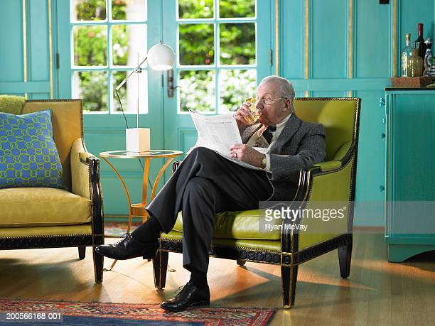 senior man sitting in armchair reading newspaper - rich old man stock photos and pictures